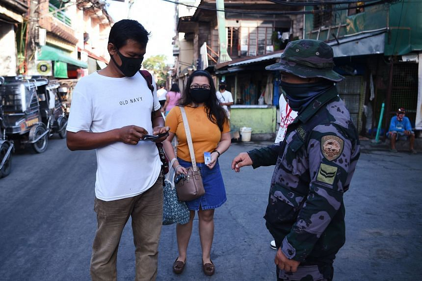 A policeman asks to see the quarantine pass of a resident in Navotas, Manila on July 16, 2020.
