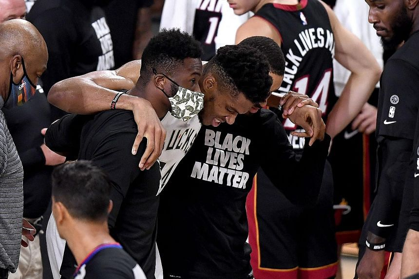 Giannis Antetokounmpo is helped off court by Bucks teammates but the East top seeds beat Miami to cut the deficit to 3-1.