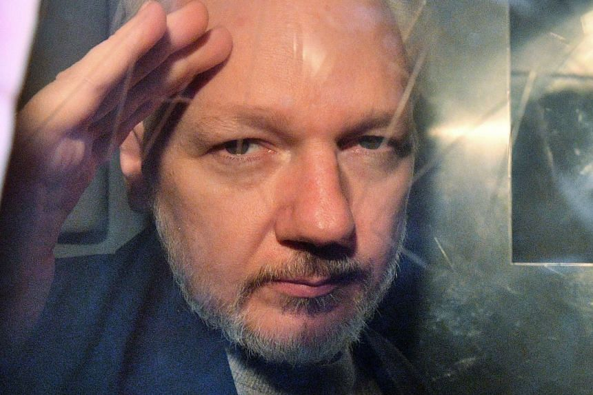 Assange gestures from the window of a prison van in May 2019.