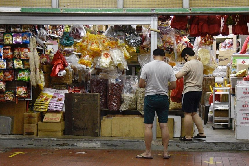 People make a purchase at a provision shop at Geylang East on May 24, 2020.