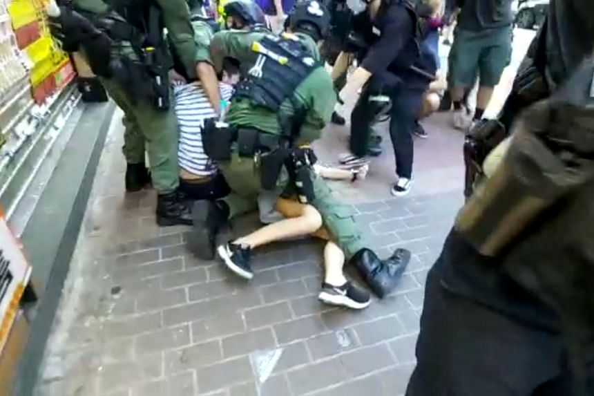 Hong Kong riot police on Sunday rounded up a group of people in Mong Kok district, including a 12-year-old girl (above) who tried to flee but was pushed to the ground and pinned down by officers (below).