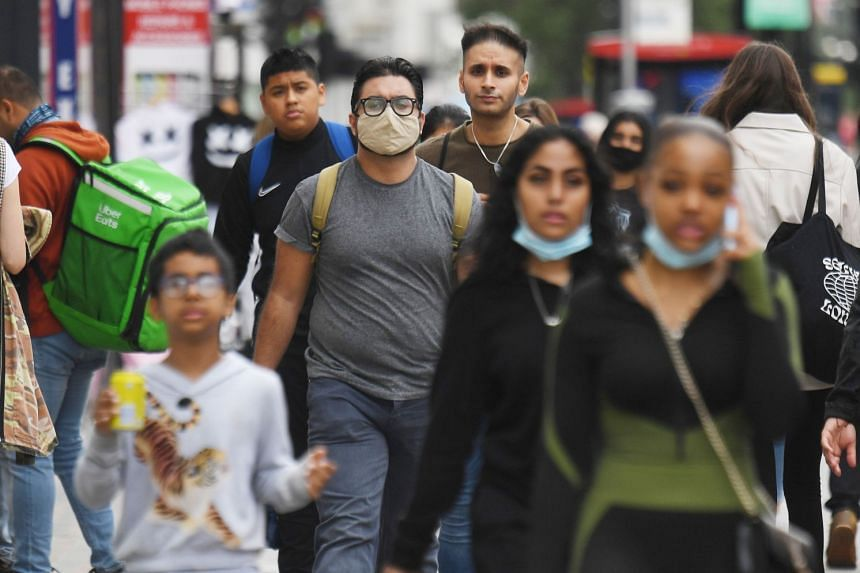 Pedestrians walk along the busy shopping area of Oxford Street in London, Sept 8, 2020.