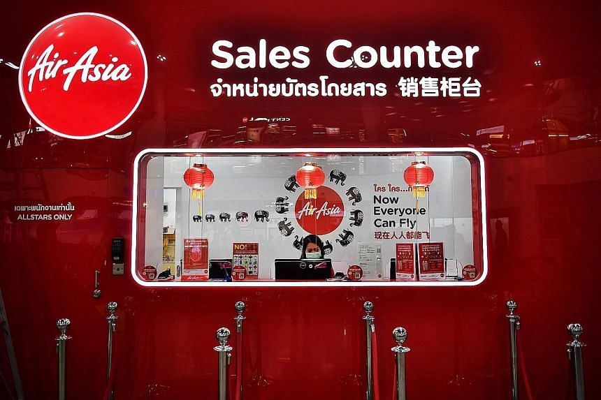An AirAsia employee manning an empty sales counter at U-Tapao Airport in Rayong, Thailand, in February. The Malaysian budget carrier, which last month posted its largest quarterly loss on record, resumed domestic operations in late April, but its lon