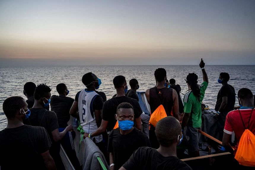 Migrants stand at sunset onboard a rescue ship off the coast of Sicily, Italy, on Aug 31, 2020.
