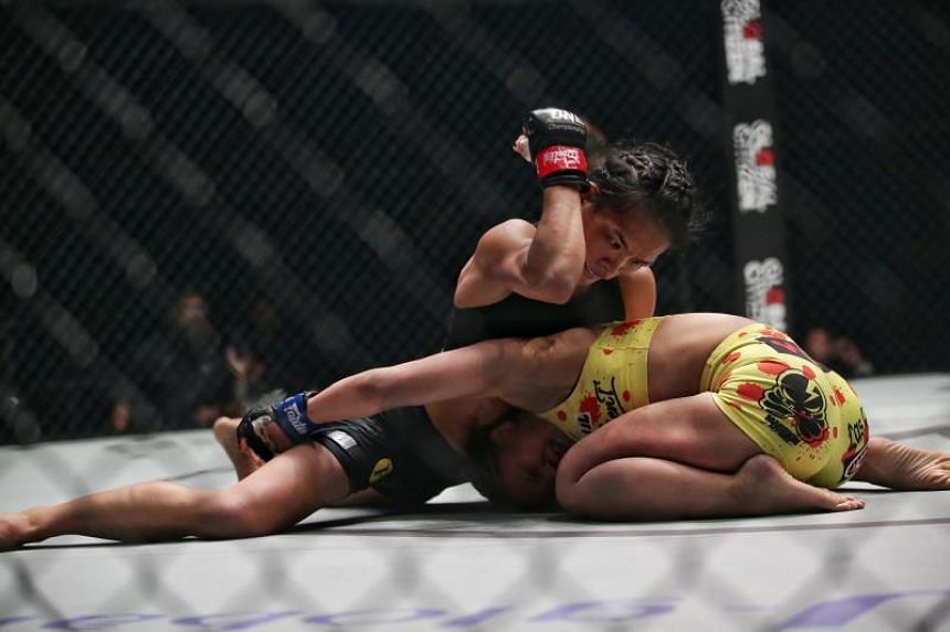 Tiffany Teo (left) throwing an elbow at Ayaka Miura during the strawweight bout in the One Championship King of the Jungle event in Singapore on Feb 28, 2020.
