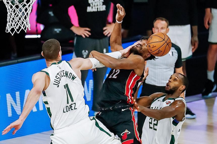 Milwaukee's Brook Lopez resorting to fouling Jimmy Butler to stop the Miami star from an easy bucket. Butler was more successful on other drives to the basket as the Heat dumped the Bucks out of the play-offs.