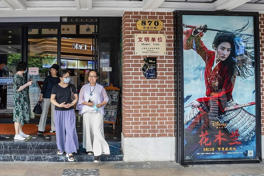 People exiting a cinema advertising the movie Mulan in Shanghai yesterday. In China, where the movie is set to open tomorrow, early viewers have also panned the film on movie review site Douban, rating it 4.7 points out of 10, accusing producers of O