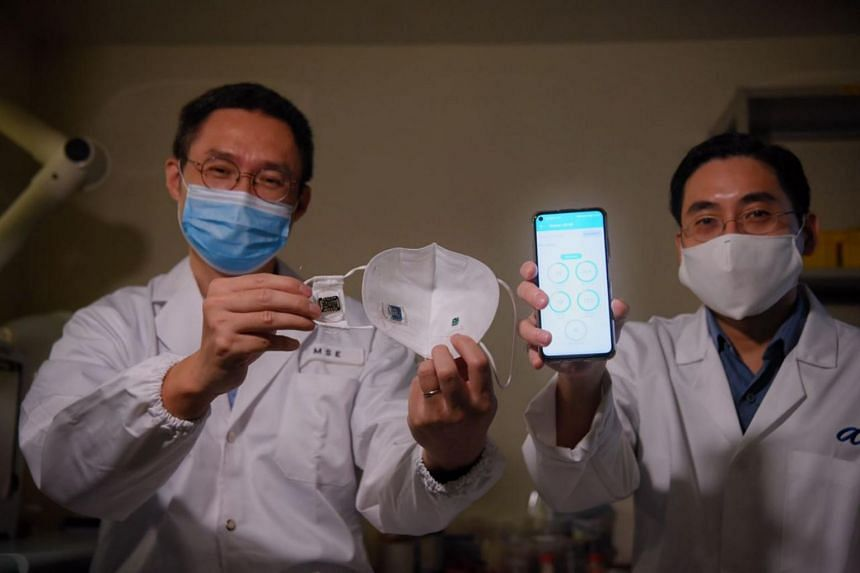 NTU's Professor Chen Xiaodong (left) displays the smart mask as A*STAR's Professor Loh Xian Jun shows a phone with the transmitted readings from the mask.