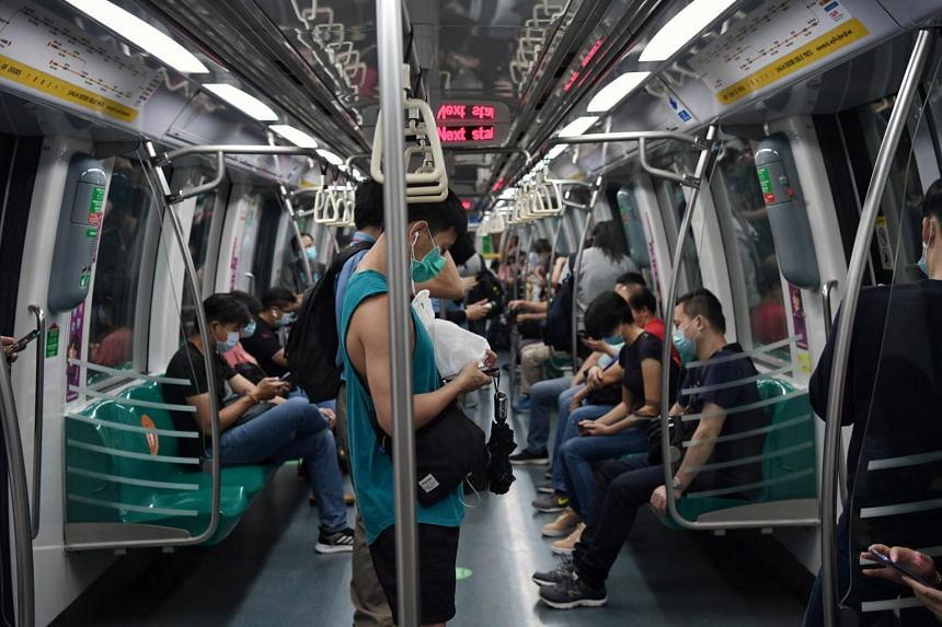 Commuters using thier mobile phones in a crowded MRT train on April 30, 2020.