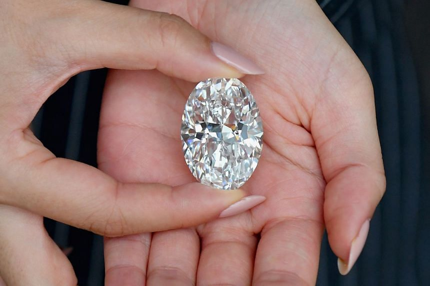 A Sotheby's employee holding the diamond during a media preview on Sept 9, 2020, in New York City.
