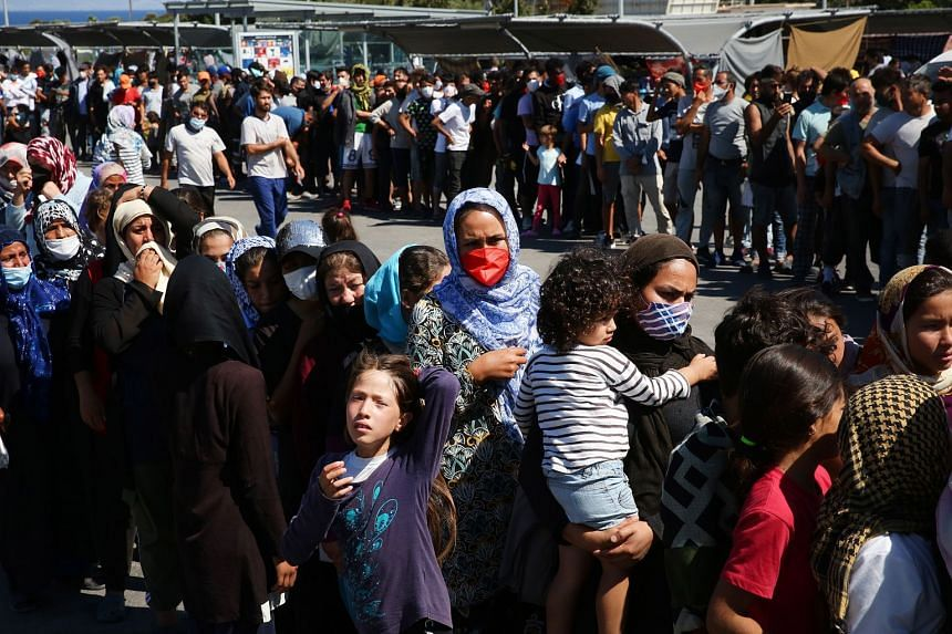 Asylum seekers wait for food, fruit and water near the Moria refugee camp on Sept 10, 2020.
