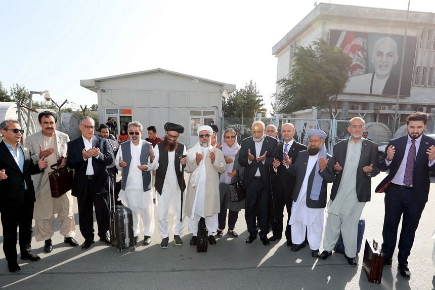 Members of Afghanistan's peace negotiation team pray as they leave Kabul for Doha on Sept 11, 2020.
