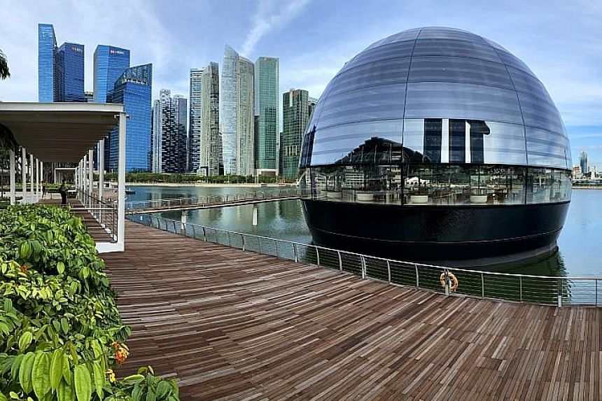 """The world's first """"floating"""" Apple store at Marina Bay Sands offers uninterrupted views of Singapore's city skyline. The igloo-like structure is made with 114 pieces of glass and held together by 10 vertical stainless steel """"ribs"""" or mullions."""