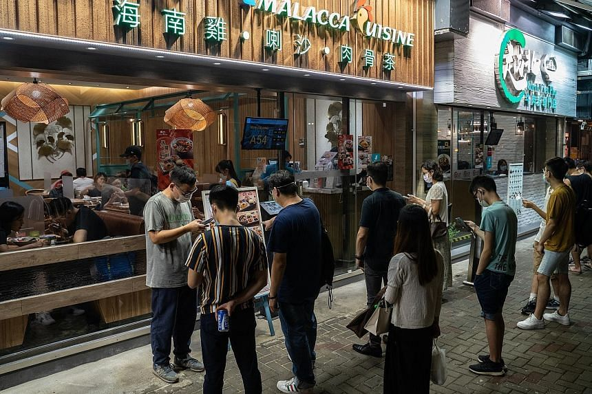 Customers waiting to enter a restaurant in the Sai Wan Ho district of Hong Kong last month. Singapore's Consulate-General in Hong Kong said that given the strong business and social ties between the two cities, the resumption of cross-border travel w