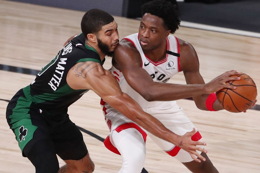 Toronto Raptors guard Kyle Lowry (right) keeps the ball away from Boston Celtics forward Jayson Tatum at the ESPN Wide World of Sports Complex on Sept 11, 2020.