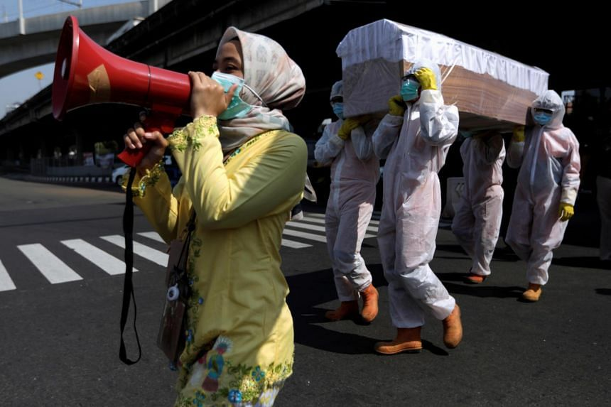 Government workers carry a mock-up of a coffin to warn people about the dangers of Covid-19 in Jakarta on Aug 28, 2020.