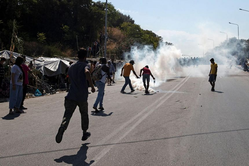 Asylum seekers throw water on tear gas fired by riot police during clashes on the island of Lesbos in Greece on Sept 12, 2020.
