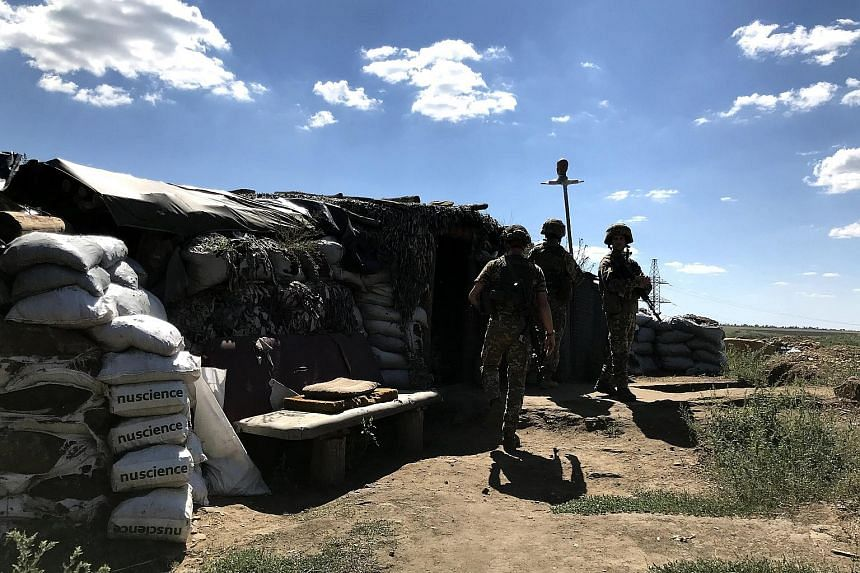 Ukrainian soldiers from the 503rd battalion walking outside a dugout right behind the zero line, in the Donbass region of eastern Ukraine, late last month. With a front line stretching nearly 500km, Ukrainian forces and Russian-backed separatists con