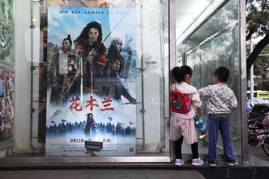 Children play next to a poster of the Disney movie Mulan outside a cinema in Beijing on Sept 11, 2020.