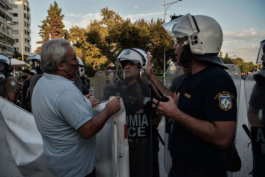 Greek riot police face demonstrators as Greek Prime Minister delivers his annual speech on defence and economic policy