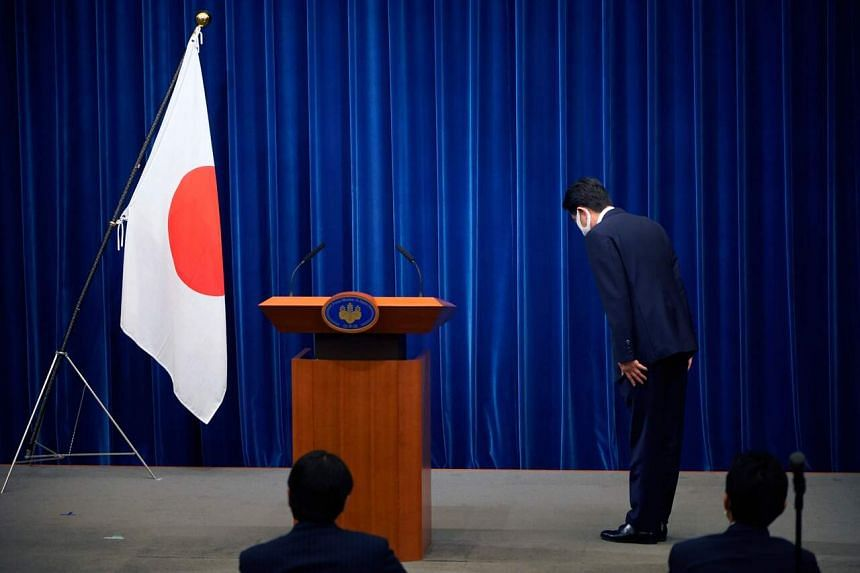 Japanese Prime Minister Shinzo Abe bowing to the Japanese flag in the prime minister's official residence in Tokyo on Aug 28 before he announced that he would resign.