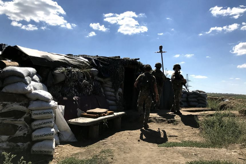 Ukrainian soldiers from the 503rd battalion walking outside a dugout right behind the zero line, in the Donbass region of eastern Ukraine, late last month.