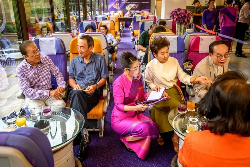 A Thai Airways flight attendant serving customers at a pop-up airplane-themed restaurant at the airline's headquarters in Bangkok on Sept 10, 2020.