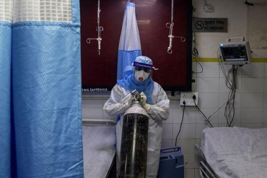 A medical worker pushes an oxygen cylinder for a patient in Lok Nayak Jai Prakash hospital in New Delhi, on July 17, 2020.