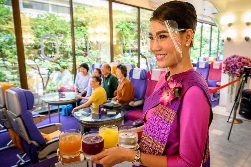 A Thai Airways flight attendant wearing a face shield as she serves drinks at a pop-up airplane-themed restaurant at the airline's headquarters in Bangkok on Sept 10, 2020.