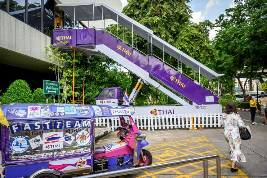 """The Thai Airways pop-up airplane-themed restaurant has a jet bridge for """"passengers"""" leading to its entrance."""