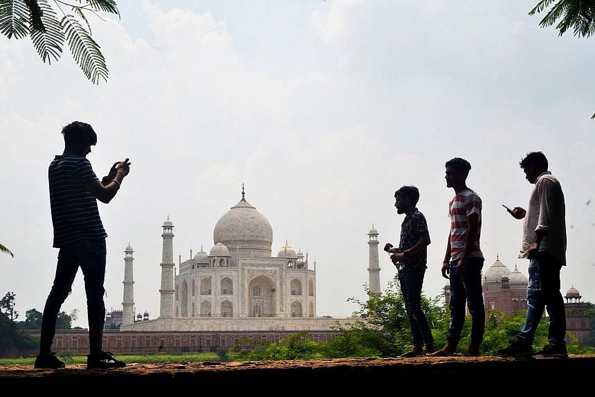 Visitors near the Taj Mahal in the city of Agra last Tuesday. States in India are taking tentative steps to attract domestic tourists to bolster revenues that took a hit when tough restrictions imposed to curb the spread of Covid-19 crippled economic