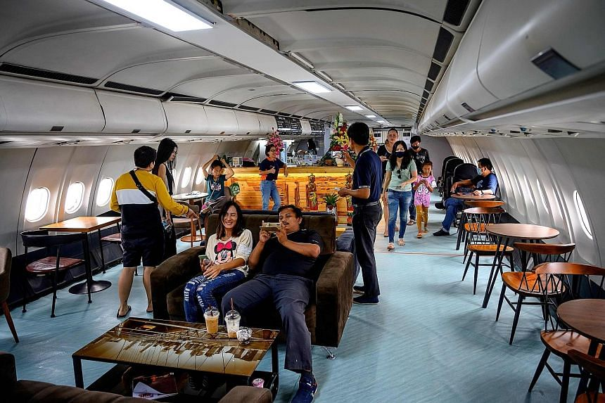 Above: A Thai Airways flight attendant serving customers at a pop-up cafe at the airline's headquarters in Bangkok. Below: Diners at a cafe built in a retired Airbus A-330 airplane, outside the coastal city of Pattaya in Chonburi province.