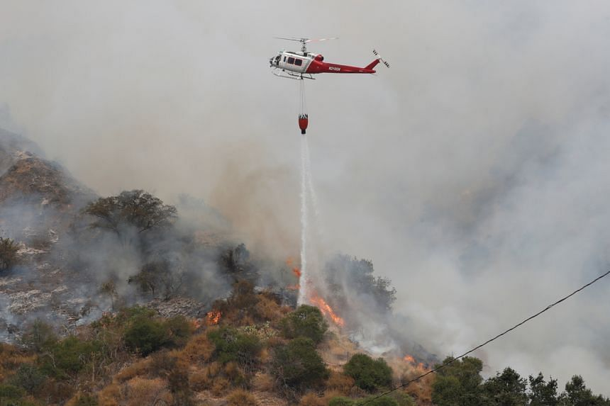 A helicopter drops water to help extinguish the Bobcat Fire in Arcadia, California, on Sept 13, 2020.