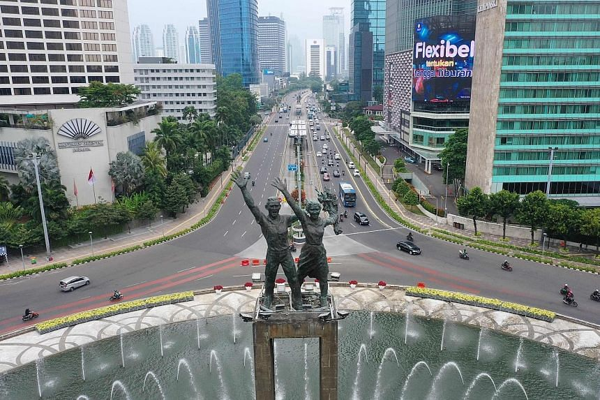 Lighter-than-usual traffic at Jakarta's Hotel Indonesia roundabout as the city went into a less restrictive lockdown yesterday. Unlike the large-scale lockdown in April, companies in non-essential sectors can continue to operate on condition that onl