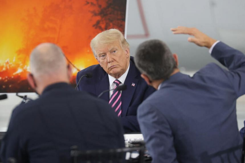 US President Donald Trump listens during a briefing on wildfires in McClellan Park, California, Sept 14, 2020.