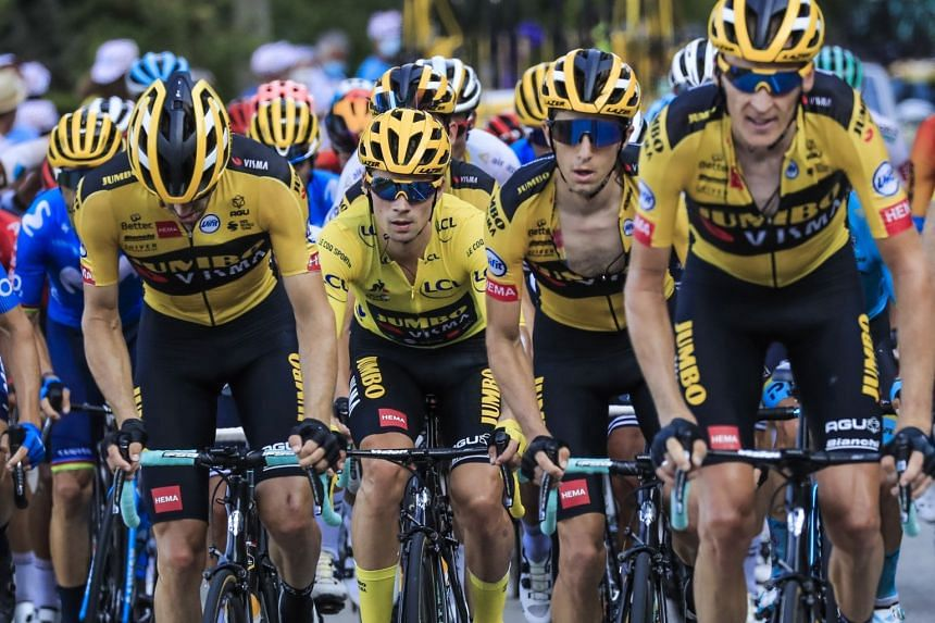Roglic (centre), wearing the overall leader's yellow jersey leads the peloton with his Team Jumbo-Visma teammates during the 16th stage.