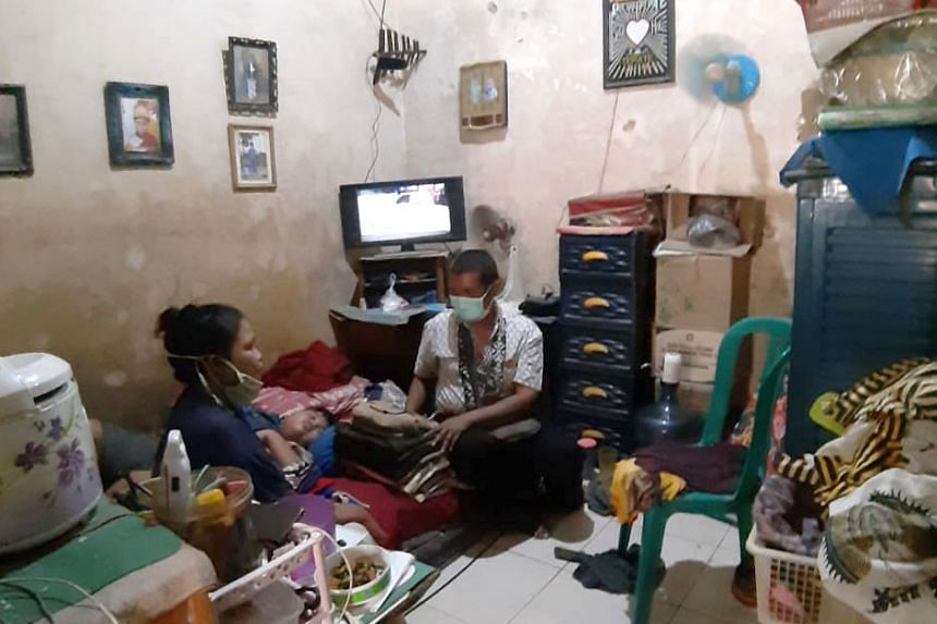 Ambulance driver Bambang Siswoyo chats with his wife at their rooming house in East Java on Sept 14.