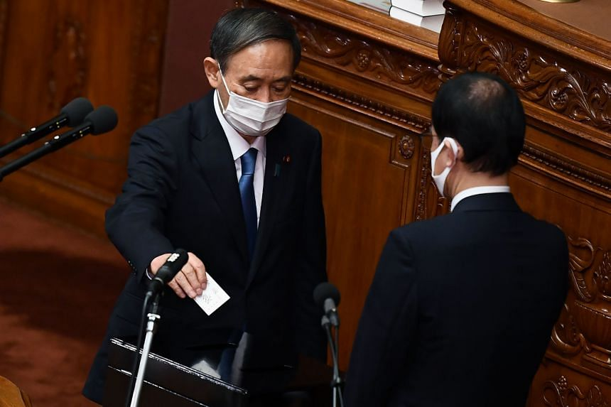 Newly elected leader of Japan's Liberal Democratic Party Yoshihide Suga (left) casts his ballot to elect the new prime minister at parliament in Tokyo on Sept 16, 2020.