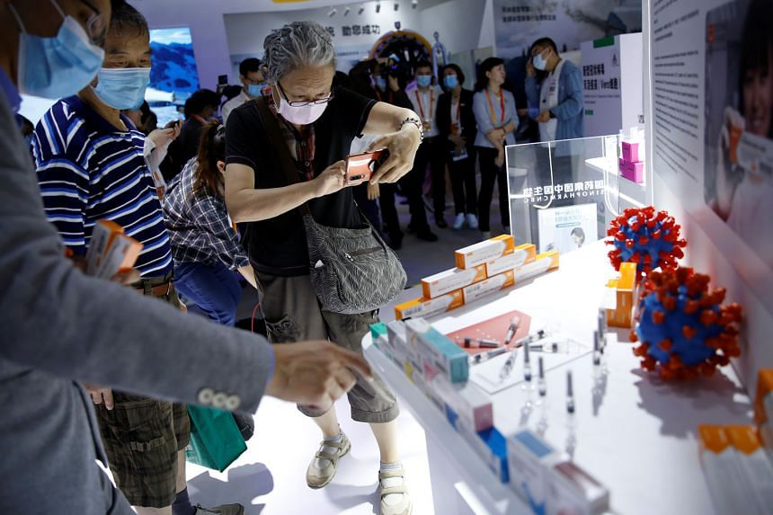 Visitors at a booth displaying a coronavirus vaccine candidate from Sinovac Biotech at the 2020 China International Fair for Trade in Services on Sept 5 in Beijing. PHOTO: REUTERS