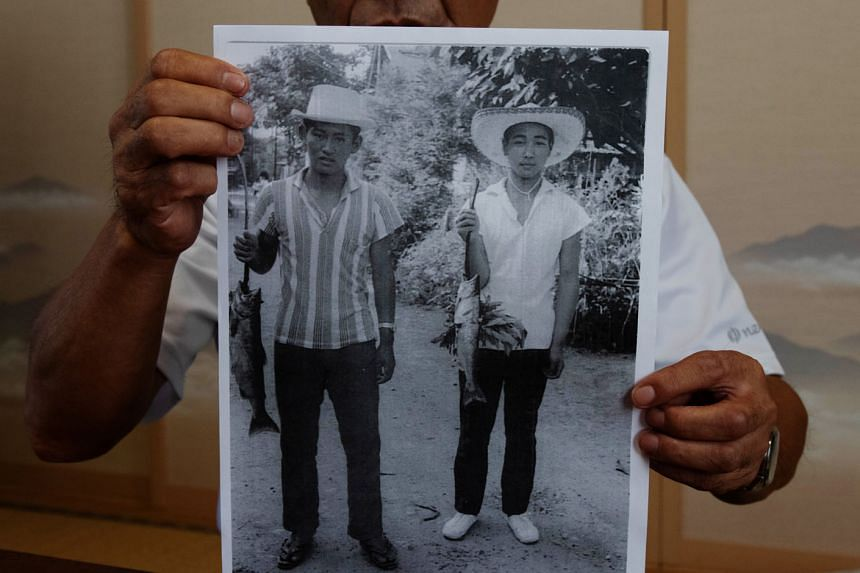 Mr Masashi Yuri, a former classmate of Mr Suga's who lived just a few houses away from him when they were growing up, with a photo showing Mr Suga (left) when he was about 15 years old.
