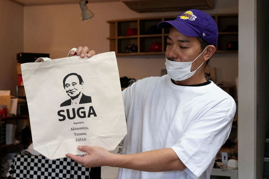 Designer Ippei Fujita, who runs a shop named Marble in Yuzawa, with a tote bag featuring Mr Suga's image. Mr Suga won a ruling party election on Monday to succeed Mr Shinzo Abe as prime minister of Japan.