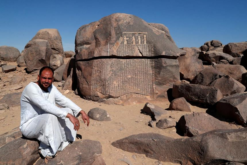 A man sits near the rock, initially attributed to the reign of King Djoser, on the Nile's Sehel Island near Aswan in southern Egypt.
