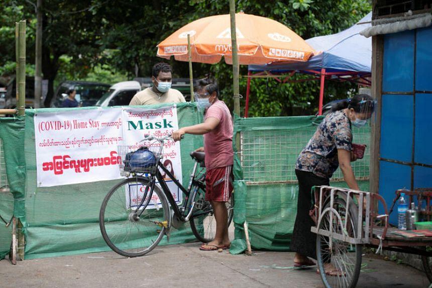 People walking past a makeshift barricade blocking a street in Yangon, Myanmar, on Sept 12, 2020.