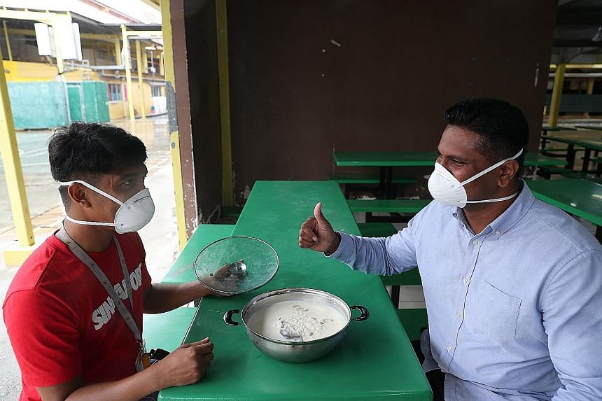 Mr Mamoun Abdulla Al (left), a worker from Bangladesh, with Mr Sheik Ismail Mohamed Ashad, a senior investigation officer with the Singapore Police Force, at the S11 Dormitory. They had got together to enjoy a pudding dish called payesh that Mr Mamou