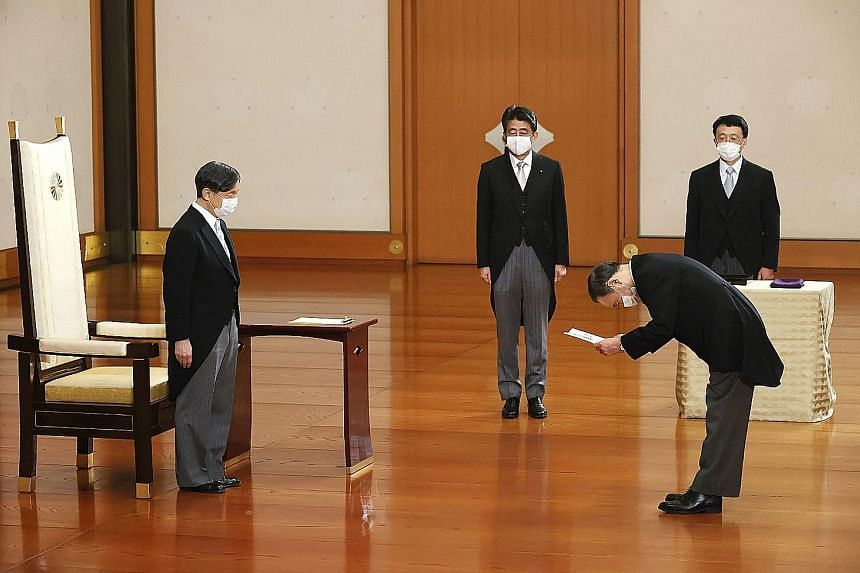 Japan's new Prime Minister Yoshihide Suga receiving a certificate from Emperor Naruhito as outgoing PM Shinzo Abe (third from right) looked on at a ceremony at the Imperial Palace in Tokyo yesterday.