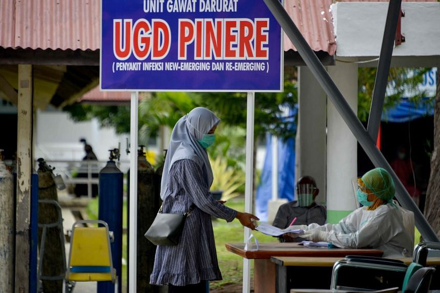 A health worker checks the identity of a woman at the Zainoel Abidin hospital in Banda Aceh, Indonesia, on Sept 16, 2020.