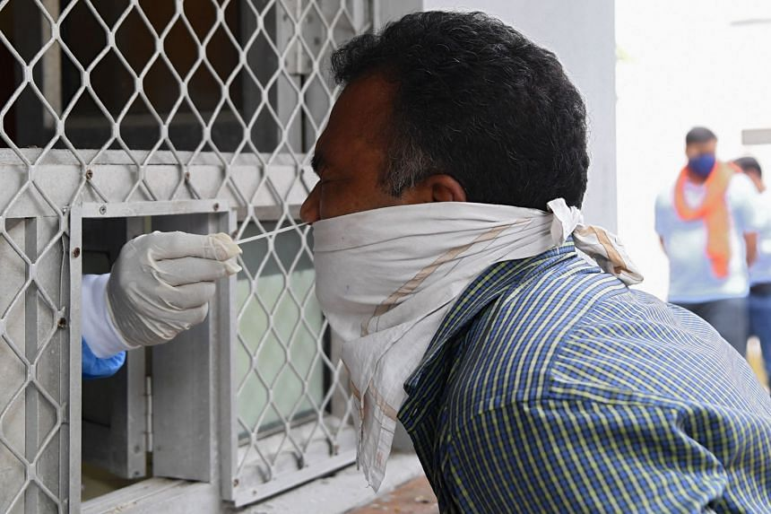 A medical worker collecting a swab sample for the coronavirus at a government health centre in New Delhi yesterday. India is now testing around a million people daily and many experts believe this is not enough. PHOTO: AGENCE FRANCE-PRESSE