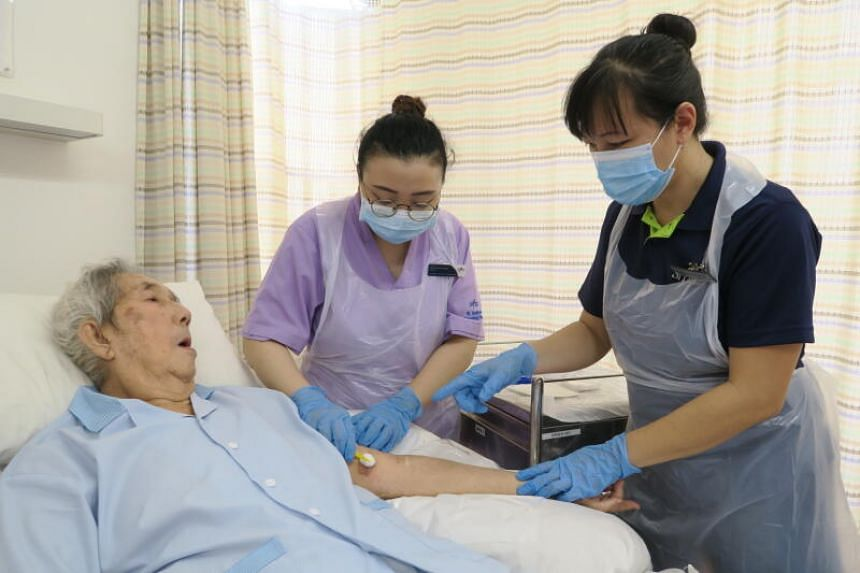 Assistant nurse clinician Caroline Tan from St Luke's Hospital (right) provides wound care training to staff nurse Naqiyah Yusuf from St Andrew's Nursing Home (Taman Jurong).