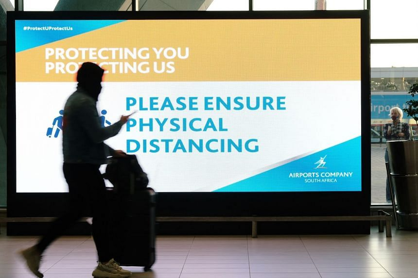 A passenger walks past a social distancing sign at Cape Town International Airport, in July 2020.