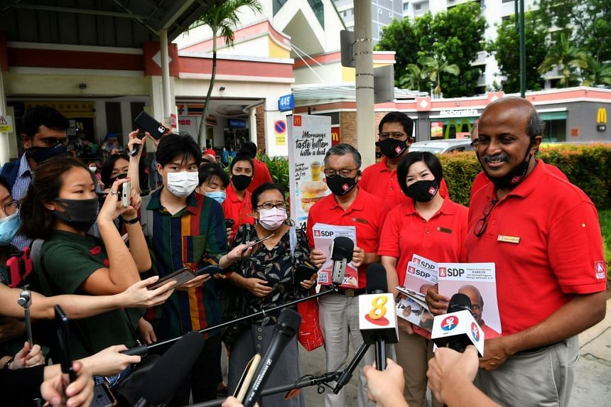 """Singapore Democratic Party candidates talk to the media during a pre-election """"drive about"""" in July 2020."""